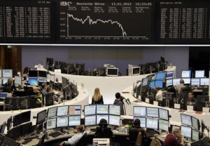 Traders are pictured at their desks in front of the DAX board at the Frankfurt stock exchange January 13, 2012.  REUTERS/Remote/Amanda Andersen  (GERMANY - Tags: BUSINESS)