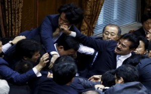 Lawmakers crowd around Yoshitada Konoike, chairman of the upper house special committee on security, as Masahisa Sato (R) of Japan's ruling Liberal Democratic Party's fist lands on opposition Democratic Party of Japan lawmaker Hiroyuki Konishi (top) during a vote at an upper house special committee session on security-related legislation at the parliament in Tokyo, Japan, September 17, 2015. A panel in Japan's upper house on Thursday approved legislation for a security policy shift that would allow troops to fight abroad for the first time since World War Two, a ruling party lawmaker said. REUTERS/Yuya Shino