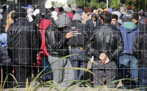 Migrants queue in the compound outside the Berlin Office of Health and Social Affairs (LAGESO) as they wait to register in Berlin, Germany, October 12, 2015. More than a million refugees will come to Germany this year, Chancellor Angela Merkel's deputy said on Sunday, as a poll showed almost half of Germans believe she is handling the influx of asylum seekers badly. German authorities are struggling to cope with the roughly 10,000 asylum seekers arriving every day. The German government still officially expects 800,000 asylum applications in 2015, while media say up to 1.5 million people could come. REUTERS/Hannibal Hanschke