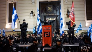Members of the extreme-right Golden Dawn party stand around a stage while leader of the  party Nikolaos Mihaloliakos delivers a speech during a gathering in Athens February 2, 2013. Photo by Milos Bicanski /Getty Images