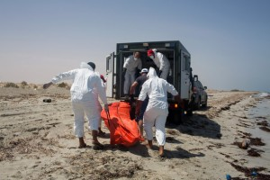 Workers for the Red Crescent carry the body of a dead migrant, in an orange body bag, to a nearby truck, at the waterfront in Zuwara, about 105 kilometers (65 miles) west of Tripoli, Libya, Friday, Aug. 28, 2015. Two ships went down Thursday off the western Libyan city, where Hussein Asheini of the Red Crescent said over 100 bodies had been recovered. About 100 people were rescued, according to the Office of the U.N. High Commissioner for Refugees, with at least 100 more believed to be missing. (AP Photo/Mohamed Ben Khalifa)