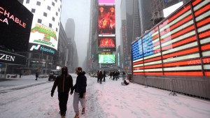 People walk through Times Square during winter blizzard that is expected to bring more than a foot of snow in New York, NY, on January 23, 2016. The National Weather Service and the Mayor of New York City have issued a winter storm warning for the five New York City boroughs. (Photo by Anthony Behar) *** Please Use Credit from Credit Field ***