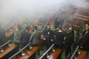 Kosovo parliament security staff wearing gas mask as opposition lawmakers release a tear gas canister disrupting a parliamentary session in Kosovo capital Pristina on Friday Feb. 19, 2016. Kosovo opposition again has used tear gas inside the Parliament disrupting its session, a repeated use of violent methods over the last five months to convince the government renounces its deals with Serbia and Montenegro. The opposition coalition has given the government an ultimatum until Feb. 27, to resign and call new elections in Kosovo. (AP Photo/Visar Kryeziu)