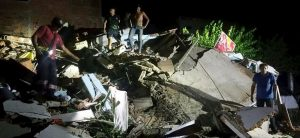 """People stand next to the debris of a building after a 7.8 magnitude earthquake struck off the country's northwest Pacific coast causing """"considerable damage"""", in Manta, Ecuador, April 16, 2016. REUTERS/Patricio Ramos EDITORIAL USE ONLY. NO RESALES. NO ARCHIVE TPX IMAGES OF THE DAY"""