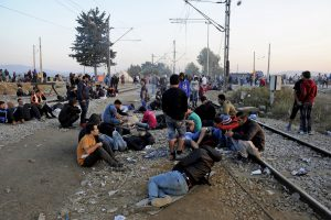 Refugees and migrants rest on railway tracks as they wait to cross the borders of Greece with Macedonia, near the village of Idomeni