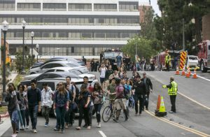 People are evacuated by Los Angeles Police officers from the UCLA campus near the scene of a fatal shooting at the University of California, Los Angeles, Wednesday, June 1, 2016, in Los Angeles. Los Angeles police chief says shooting at UCLA was murder-suicide. (AP Photo/Damian Dovarganes)