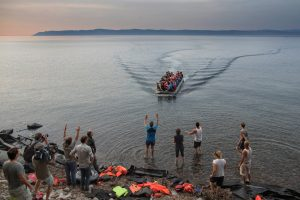 Press, volunteers and locals greet an inflatable boat carrying Syrian refugees as it arrives on the northern shore of the island of Lesbos in the evening. There is hardly any organised help for the refugees in Lesbos.  Volunteers from the UK, the Netherlands, Denmark and Norway are among the people who provide water, dry clothes and assistance for the newly arrived refugees. Around 2.000 refugees arrive on Lesbos island on most days.   The summer of 2015 saw a huge increase in the number of migrants and refugees arriving in Italy and Greece, wanting to enter the European Union and make their way to Northern Europe to find work or claim asylum. Greece has become a major transit country for people making the short crossing from the Turkish mainland to Greek islands near the Turkish coast.