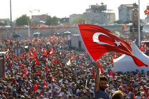 A man waves Turkey's national flag as he with supporters of various political parties gathers in Istanbul's Taksim Square