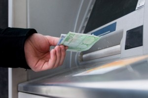 epa01588989 A young man withdraws euro notes from a cash machine in Bratislava, Slovakia on 01 January 2009. Slovakia has become the 16th member of the eurozone, the second former communist country to join the grouping on 01 January 2008. The Slovak koruna (crown) will remain in circulation alongside the euro until 16 January.  EPA/PETER HUDEC