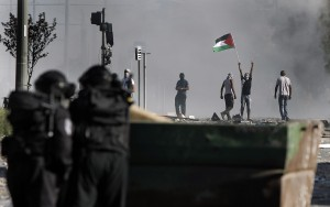 Masked Palestinian protesters throw stones towards Israeli police during clashes in the Shuafat neighborhood in East Jerusalem, on July 3, 2014. one day after a Palestinian teenager was kidnapped and killed in an apparent act of revenge for the murder by militants of three Israeli youths. AFP PHOTO / AHMAD GHARABLI        (Photo credit should read AHMAD GHARABLI/AFP/Getty Images)