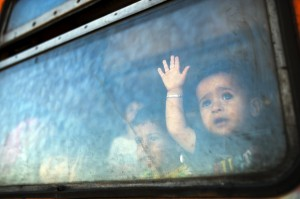 A migrant boy looks through a window onboard a train for Serbia at the new transit center for migrants at the border line between Greece and Macedonia near the town of Gevgelija on August 28, 2015. Serbia and Macedonia's foreign ministers called for EU action on Europe's migrant crisis at a summit on August 27 of leaders from the western Balkans, attended by German Chancellor Angela Merkel. Both have become major transit countries for tens of thousands of migrants trying to reach the European Union in recent months, with Macedonia last week forced to declare a state of emergency. AFP PHOTO / ROBERT ATANASOVSKI