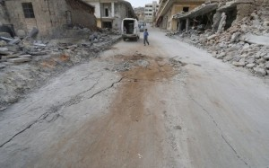 A boy walks near damaged ground at a site hit by what residents said were airstrikes carried out by the Russian air force in the town of Darat Izza in Aleppo's countryside October 13, 2015. REUTERS/Ammar Abdullah