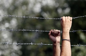 A man holds the fence and looks over at the Horgos border crossing into Hungary, near Horgos, Serbia, Wednesday, Sept. 16, 2015. Small groups of migrants continued to sneak into Hungary on Wednesday, a day after the country sealed its border with Serbia and began arresting people trying to breach the razor-wire barrier, while a first group arrived in Croatia seeking another way into the European Union. (AP Photo/Darko Vojinovic)