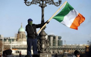 A demonstrator waves the national flag as people gather to protest against austerity policies and increases in water bills, according to local media, in central Dublin January 31, 2015.  REUTERS/Cathal McNaughton