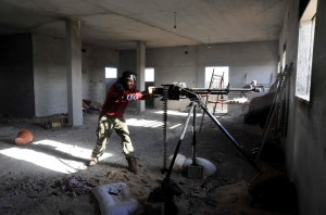 """In this picture taken Thursday, March 10, 2016, fighters against the Islamic State group fire weapons in the Hawari area, south-west of the city of Benghazi, Libya.  The leader of Islamic State group in Libya says the North African country has become a """"destination"""" for jihadists, with the numbers of fighters having doubled in recent months, but added that his group has struggled to spread across Libya because of rivalries between militants. (ANSA/AP Photo/Mohammed El-Shaiky)"""