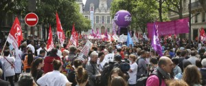 """Technicians and nurses demonstrate in Paris, France, Thursday May 28, 2015, outside the headquarters of Paris' regional hospital authority. Thousands of doctors, nurses and other hospital personnel are demonstrating in central Paris to protest a planned working-hours reform they say will result in more burnout and worse patient care. Banners with slogans like """"Taking away our rights never made the economy grow"""" lined the roadway near the city's Renaissance-style city hall, visible in background. (AP Photo/Remy de la Mauviniere)"""