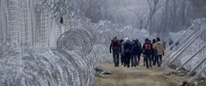Refugees and migrants, who entered Macedonia from Greece illegally, walk between the two lines of the protective fence along the border line, near southern Macedonia's town of Gevgelija, Monday, Feb. 29, 2016. Macedonia is restricting the entry of refugees to match the number of those leaving the country, allowing in only refugees from Syria and Iraq, in response to bottlenecks further up along the Balkans migrant route. (AP Photo/Boris Grdanoski)