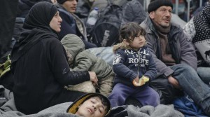 Migrants wait by the border gate between Greece and Macedonia at the northern Greek border station of Idomeni, Monday, March 7, 2016. Greek police officials say Macedonian authorities have imposed further restrictions on refugees trying to cross the border, saying only those from cities they consider to be at war can enter as up to 14,000 people are trapped in Idomeni, while another 6,000-7,000 are being housed in refugee camps around the region.(AP Photo/Vadim Ghirda)