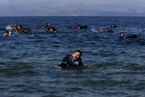 Refugee reacts from exhaustion while swimming towards the shore after a dinghy carrying Syrian and Afghan refugees deflated some 100m away before reaching the Greek island of Lesbos