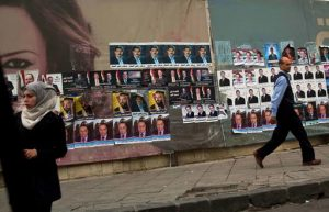 Syrians pass by campaign posters for parliamentary candidates in Damascus, Syria, Tuesday, April 12, 2016. Parliamentary elections will be held in Syria to elect the People's Council on 13 April 2016. The vote - expected to be a rubber stamp of President Bashar Assad's loyalists - will only proceed in government-controlled areas as the Damascus authorities are unable to organize any balloting in rebel-controlled areas or the territory under the Islamic State group. (AP Photo/Hassan Ammar)