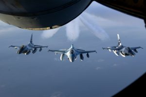 Three F-16 Fighter jets flies in formation on their way to a new home behind a KC-135 Stratotanker after their refueling on January 20, 2008. Eielson AFB and Kunsan Air Base swapped seven F-16 jets as a part of the Common Configuration Implementation Program (CCIP). (U.S. Air Force photo by: Staff Sgt. Eric T. Sheler)