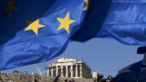 "A Greek national flag flies beneath the Parthenon temple on Acropolis hill in Athens, Greece, on Tuesday, May 1, 2012. It is ""entirely possible"" IMF, EU will refuse to make next payment to Greece if new govt doesn't fulfill its commitments, UBS's Stephane Deo says in note to clients before May 6 elections. Photographer: Simon Dawson/Bloomberg"
