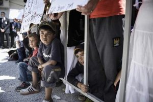 "In this photo released by Greek Prime Minister's office on Saturday, April 16, 2016, refugees and migrants look on during a visit by Ecumenical Patriarch Bartholomew I, Pope Francis, and Greek Orthodox Archbishop Ieronymos at the Moria refugee camp on the island of Lesbos, Greece. Pope Francis implored Europe on Saturday to respond to the migrant crisis on its shores ""in a way that is worthy of our common humanity,"" during an emotional and provocative trip to Greece.  (Andrea Bonetti/Greek Prime Minister's Office via AP)"