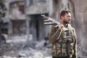 A FREE SYRIAN ARMY FIGHTER HOLDS HIS RIFLE AS HE STANDS ON A DAMAGED STREET  IN ALEPPO'S KARM AL-JABAL DISTRICT