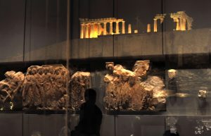 Fragments of the Parthenon frieze are reflected in the windows of the Parthenon hall at the new Acropolis museum during its official opening on June 20, 2009 in Athens as the Acropolis stands in the background. Designed by celebrated Franco-Swiss architect Bernard Tschumi, the three-level building set out over a total area of 25,000 square metres (270,000 square feet) will display more than 350 artefacts and sculptures that were previously held in a small museum atop the Acropolis. AFP PHOTO / LOUISA GOULIAMAKI