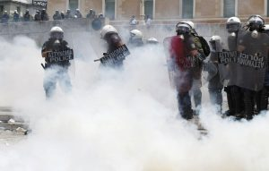 Riot police surrounded by teargas in front of the parliament in Athens