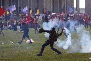 An anti-government demonstrator throws back a tear gas canister during a clash with riot policemen during a protest against a constitutional amendment, known as PEC 55, that limits public spending, in front of Brazil's National Congress in Brasilia, Brazil November 29, 2016. REUTERS/Adriano Machado